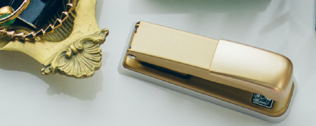 gold stapler and bowl of jewelry