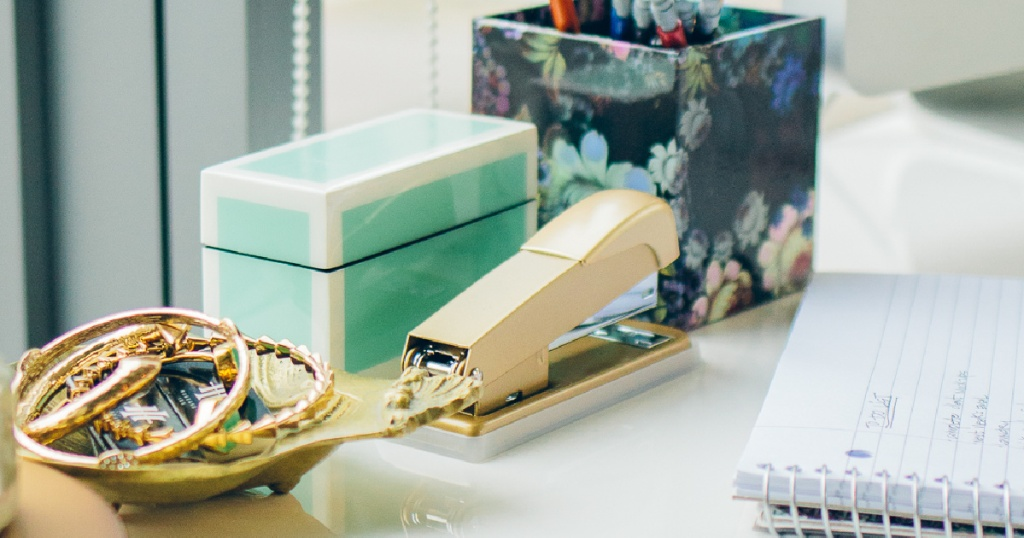 gold stapler, notebook, jewelry bowl, and more on desk