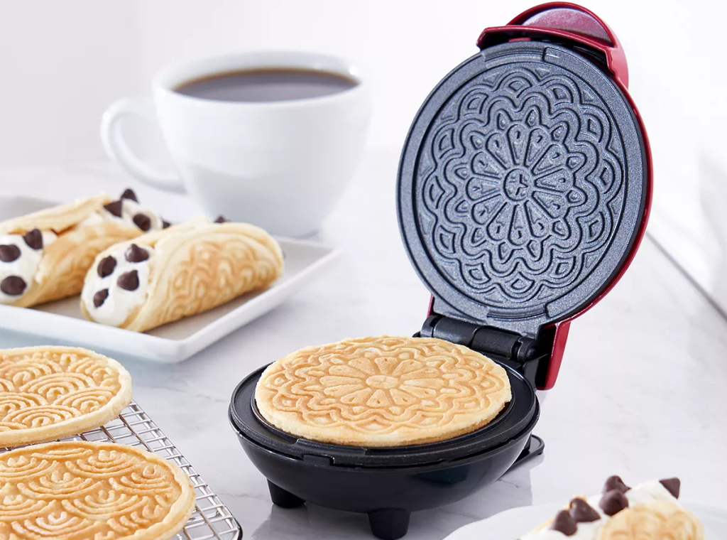 Dash Pizzelle Maker with pizzelles next to it