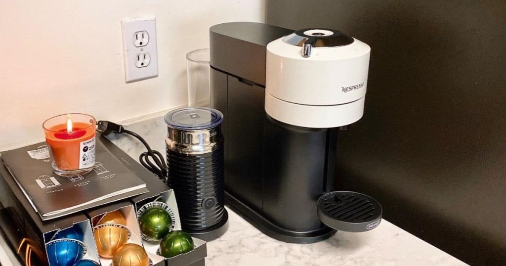 white and black Nespresso machine with frother and capsules on kitchen counter
