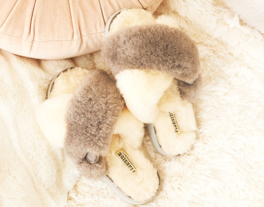 pair of fuzzy white and grey slipper slides on a white bed
