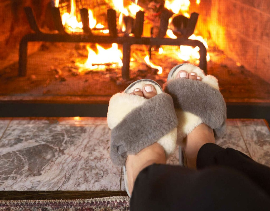 woman putting her legs up near a fireplace with a pair of fuzzy grey and white slipper slides on her feet