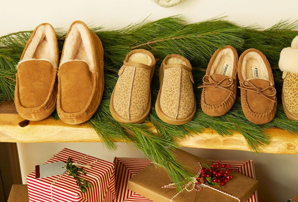 pairs of men and women's moccasins and kids leopard print slippers on bench with greenery and christmas presents
