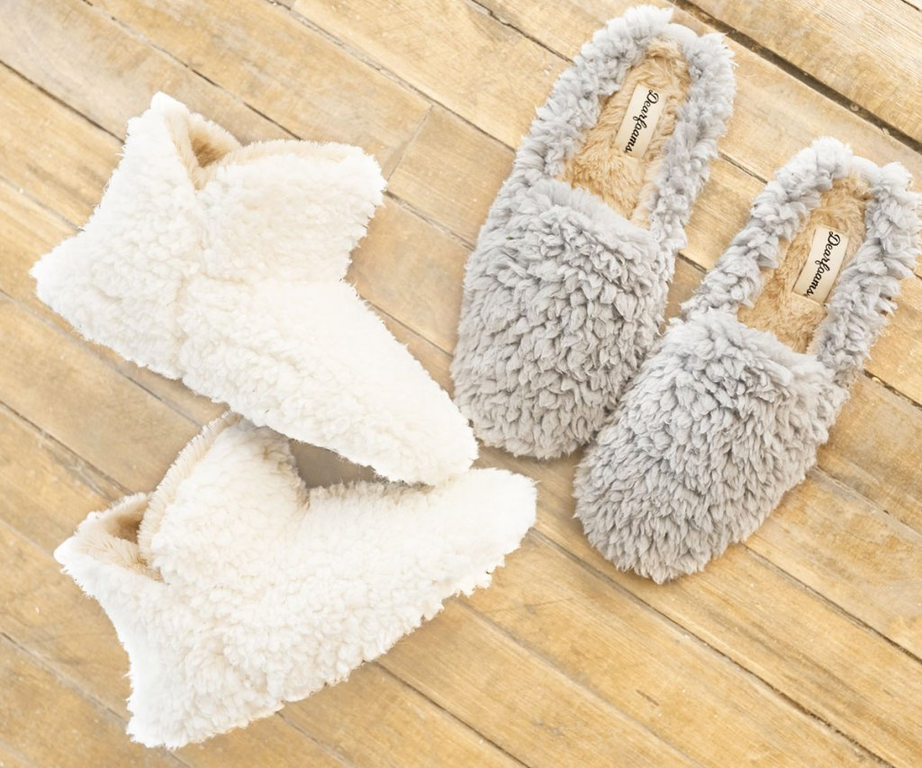 pair of white bootie fuzzy slipper boots and slip on fuzzy slippers laying on wood floor