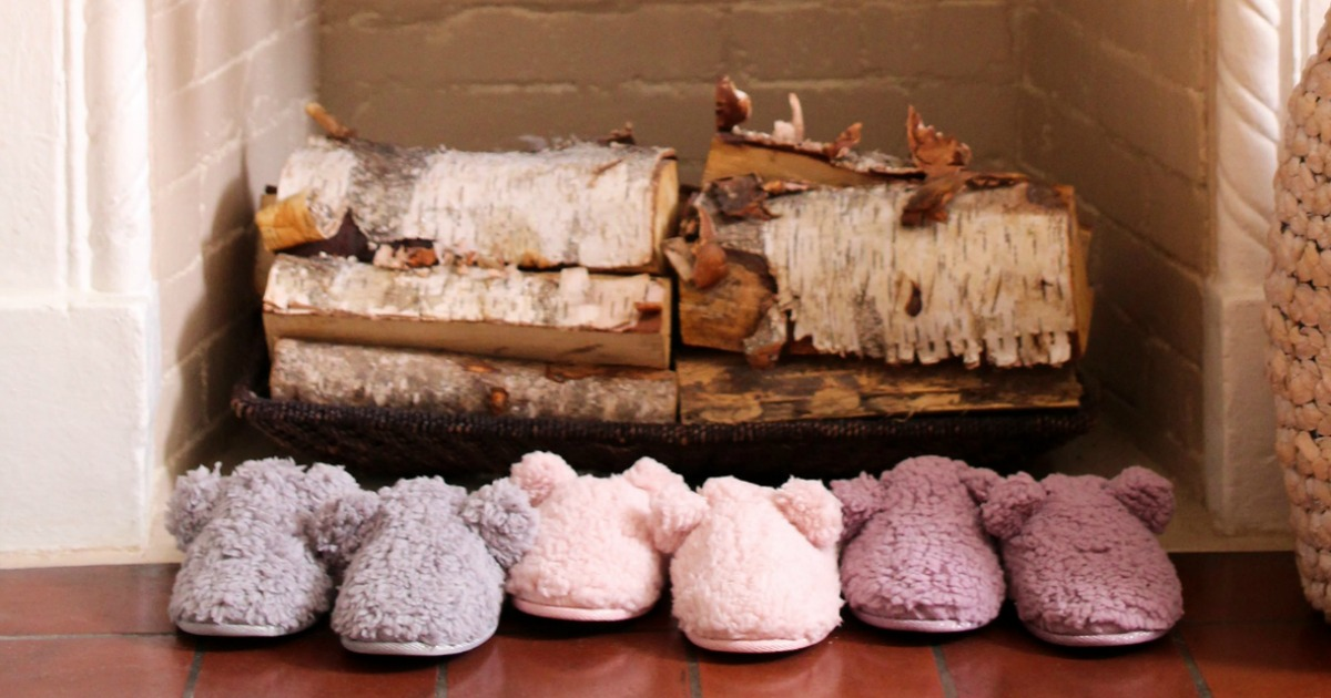 A variety of kids slippers near a fire place