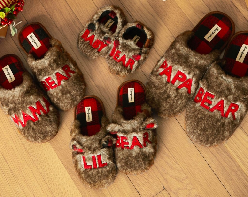 four pairs of matching family brown fuzzy bear slippers on wood floor