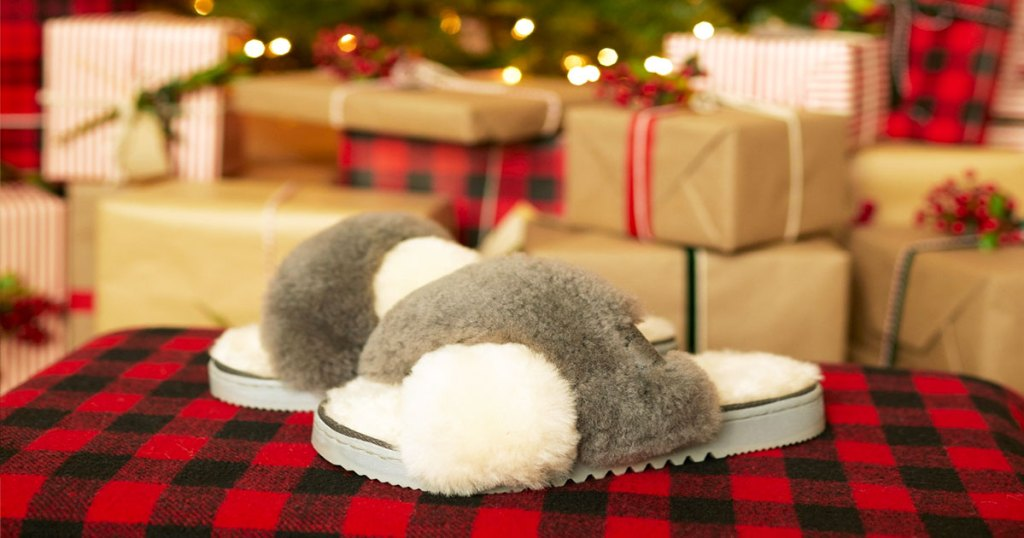 pair of grey and white fuzzy slipper slides on red and black buffalo check table with christmas tree and presents in background