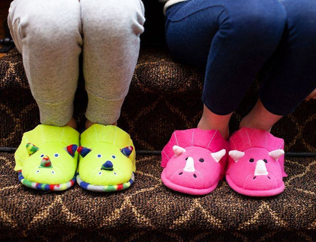 two kids sitting on stairs wearing sweatpants and green and pink dinosaur slippers