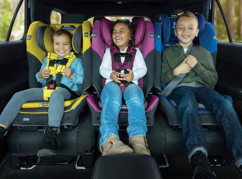 tiga anak di kursi mobil di dalam mobil