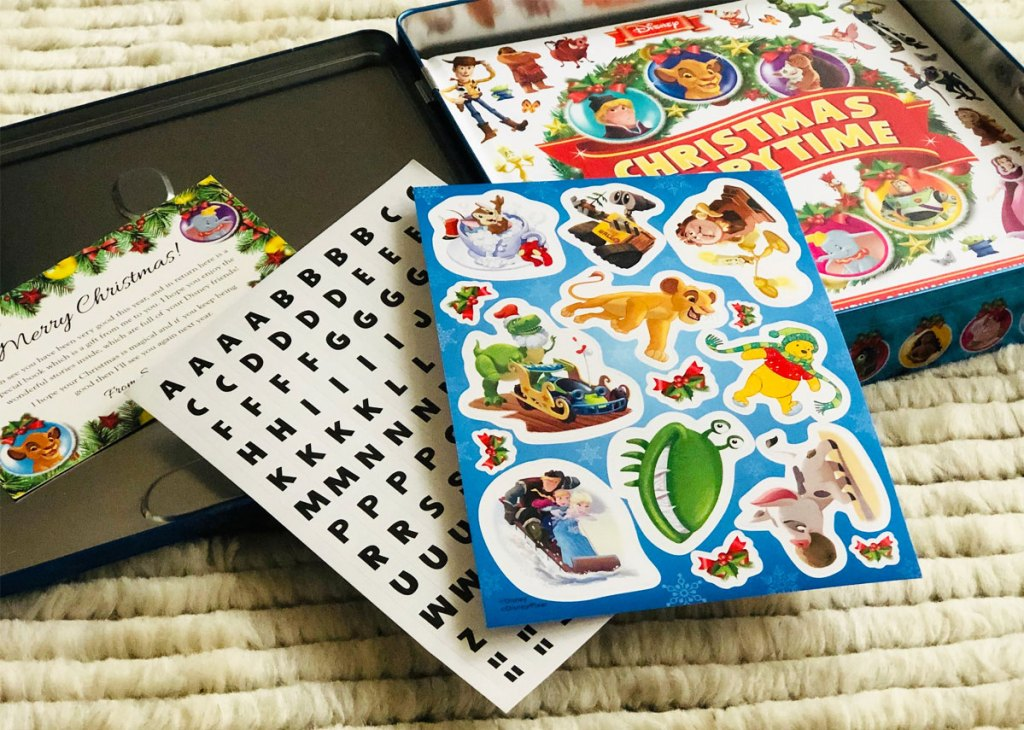 disney countdown to christmas tin opened on floor with book and sheets of stickers inside