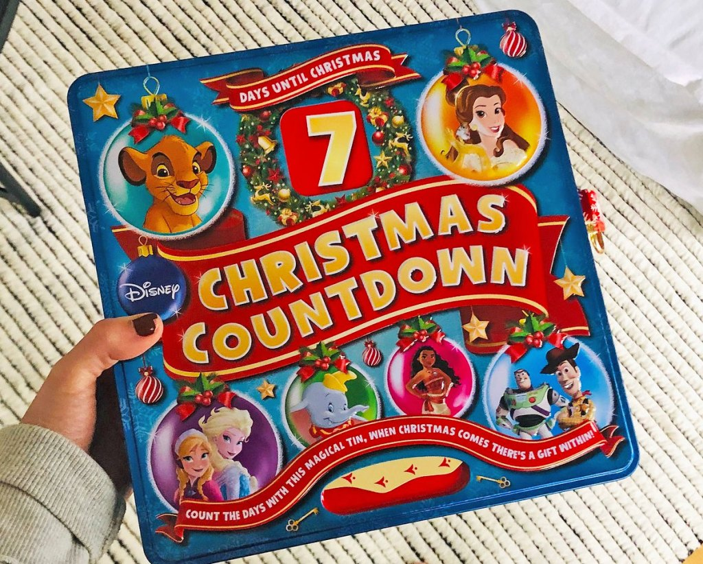 woman holding up a blue and red disney countdown to christmas tin