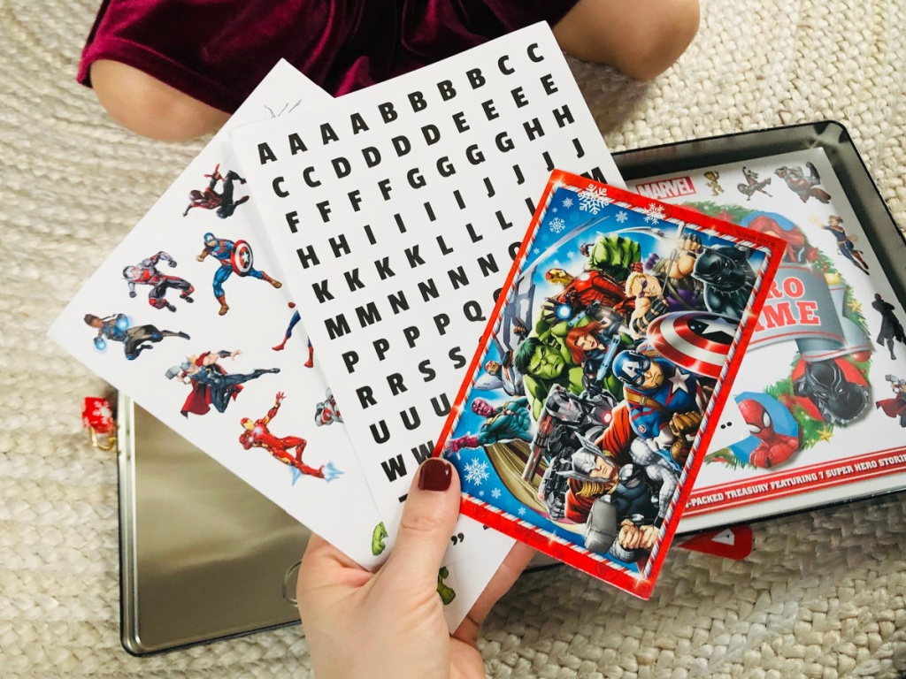 hand holding marvel cards and stickers from marvel advent tin calendar