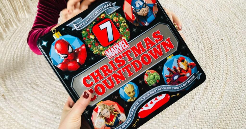 woman's hand holding a marvel countdown calendar tin