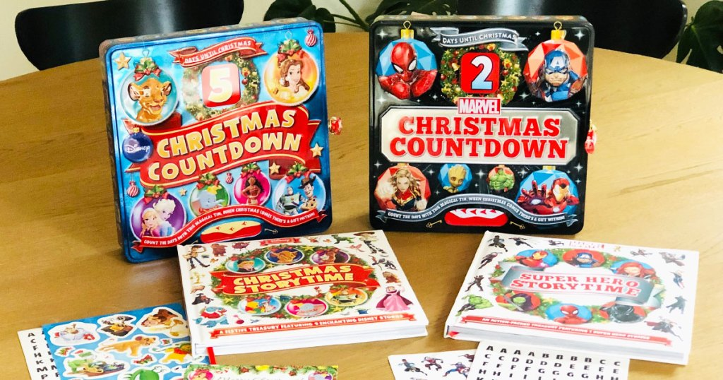 disney and marvel countdown to christmas tins on table with books and stickers in front of them
