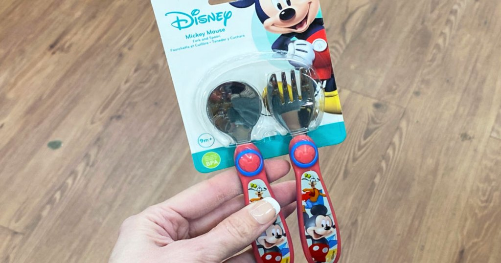 woman holding up a red and blue set of mickey mouse and goofy themed baby flatware