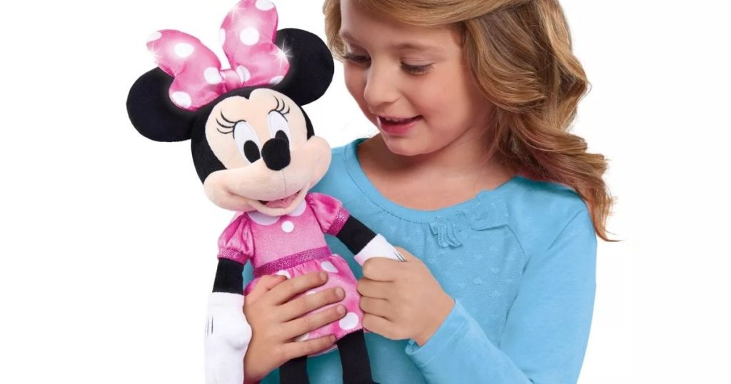 girl holding Disney Minnie Lights and Sounds Plush