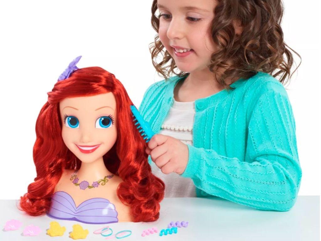 little girl brushing Ariel styling head