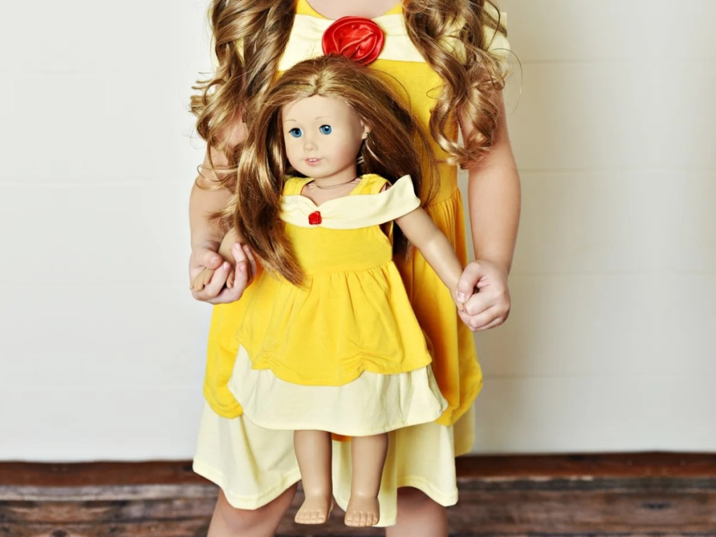 girl in Belle princess dress holding doll in matching dress