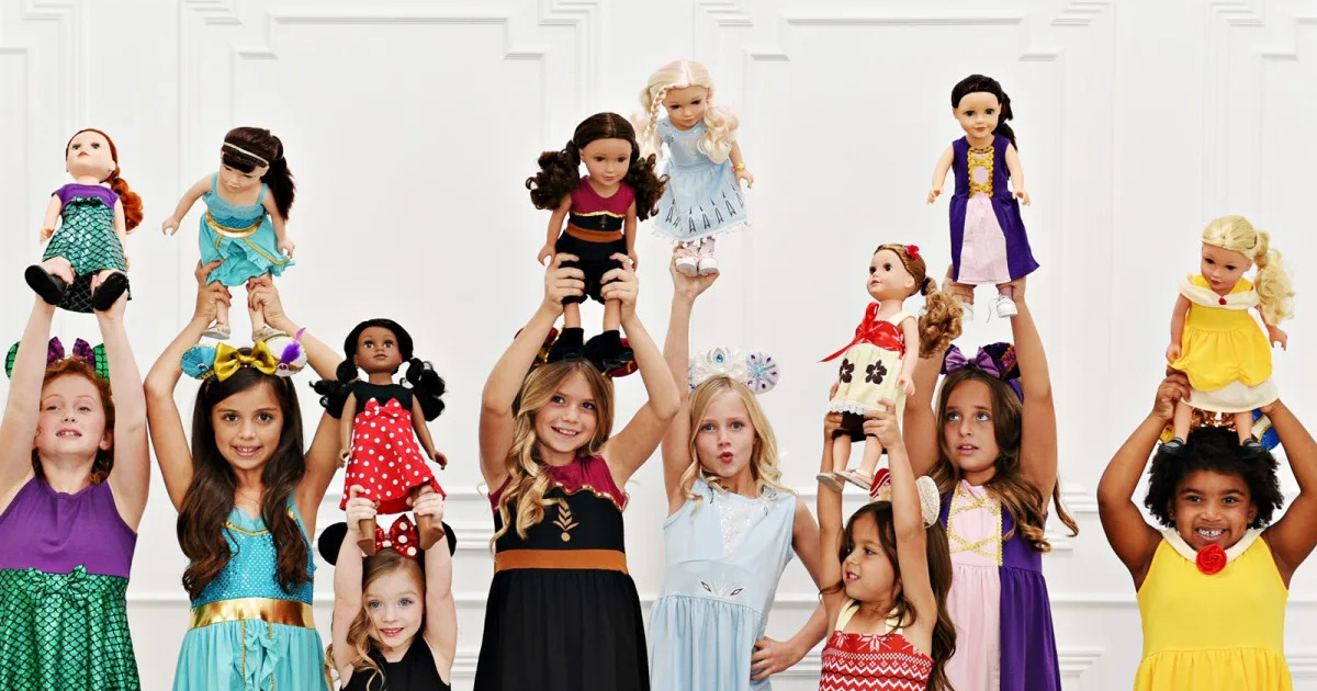group of girls in princess dresses holding dolls with matching dresses