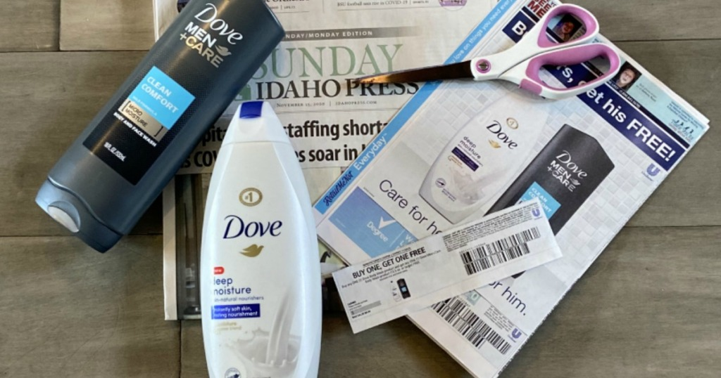 Buy 1 Get 1 Free Dove Body Wash Coupon on top of newspaper with scissors