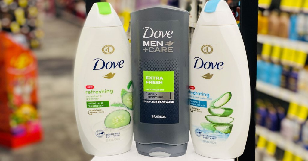 two white bottles of dove women's body wash and one grey bottle of dove men's body wash on white table at cvs