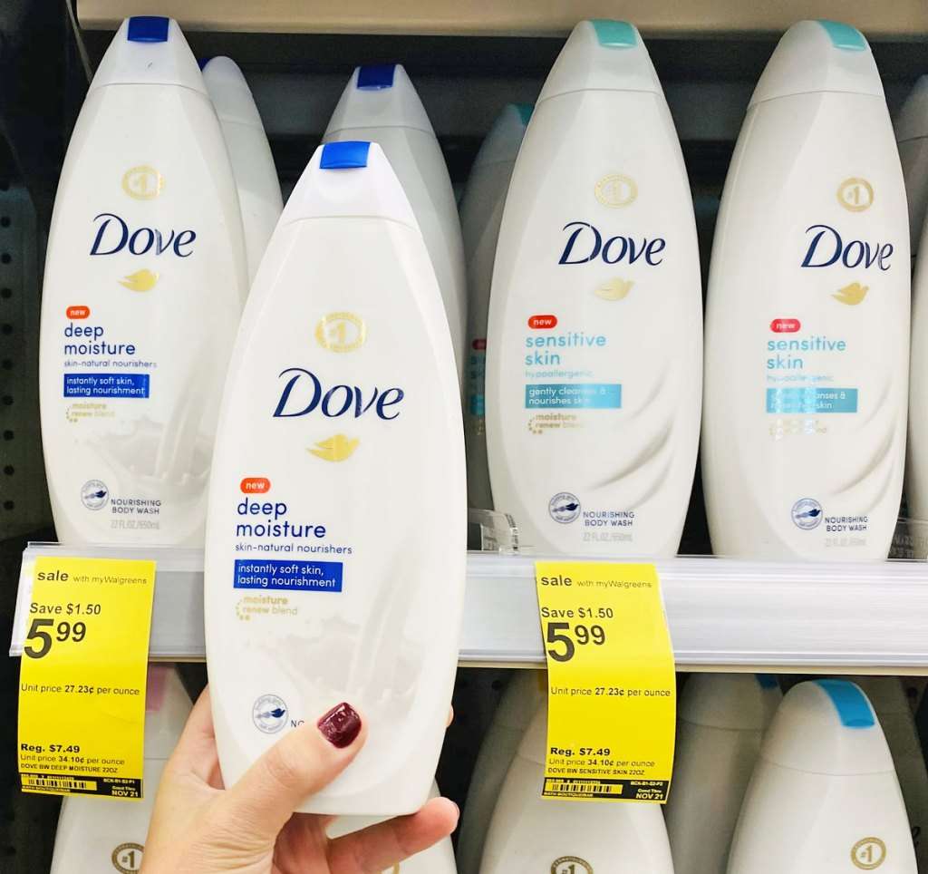 woman with dark red nails holding up a bottle of dove body wash in front of walgreens shelf full of bottles of dove body wash