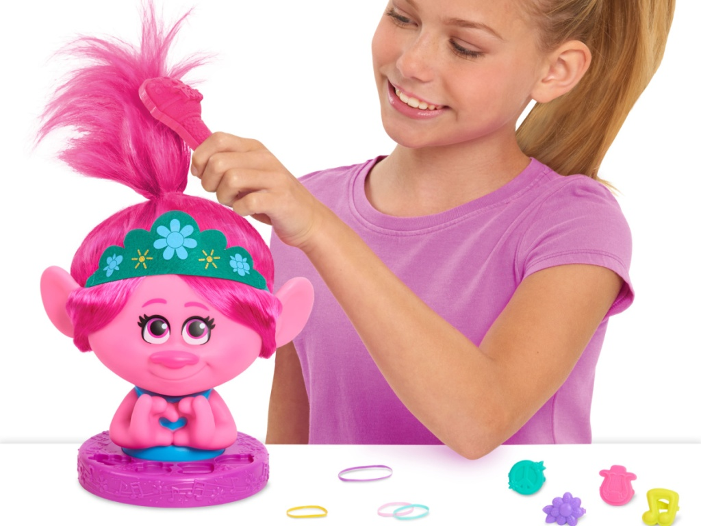 girl playing with pink troll styling head and accessories