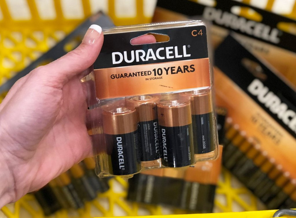 woman holding up 4-pack of duracell C batteries in front of other types of duracell batteries in yellow shopping basket