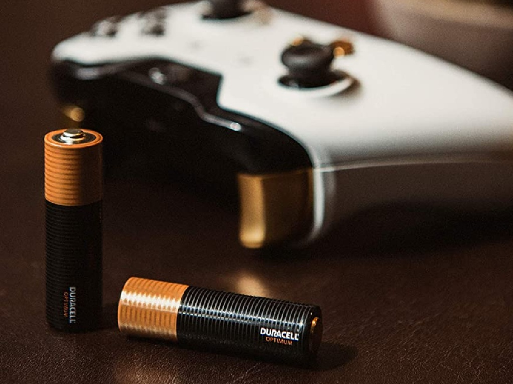two batteries and white xbox controller on table