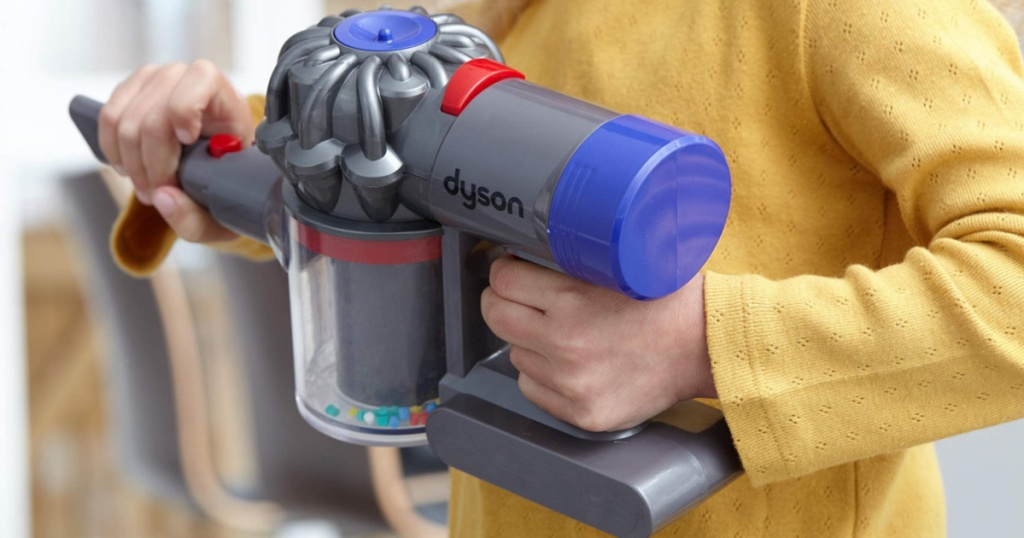 little girl holding a shortened Dyson kids stick vacuum