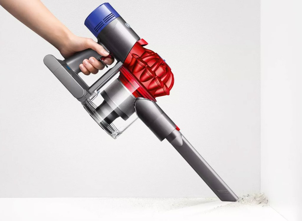 person holding a grey and red dyson handheld vacuum to clean dust in a corner