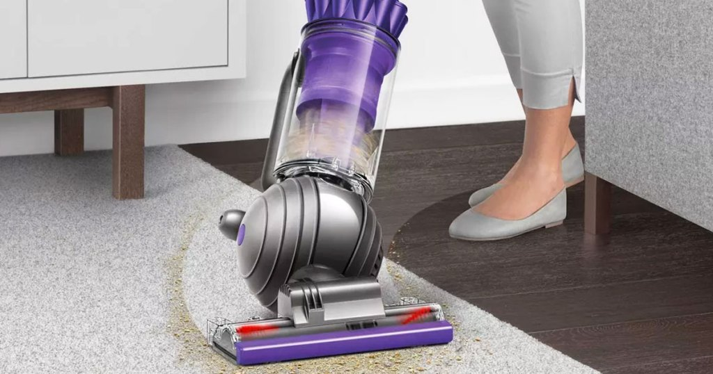 woman using a dyson ball upright vacuum to clean up dust around a couch