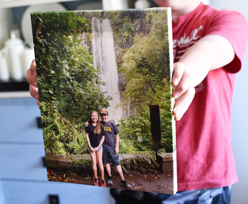 boy in red shirt holding up a canvas photo print of boy and girl standing in front of waterfall