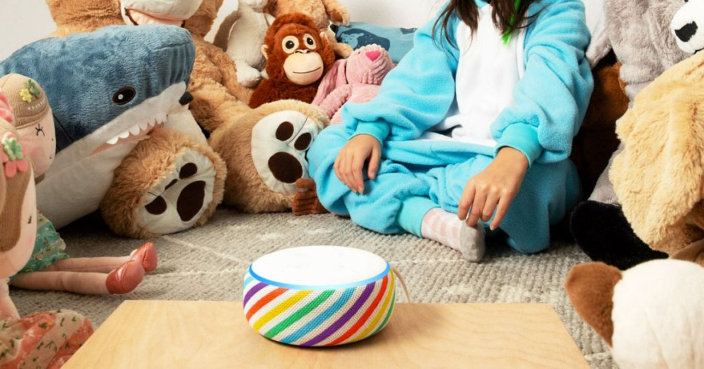 rainbow stripe echo dot on a wood table with a girl in pajamas surrounded by stuffed animals in the background
