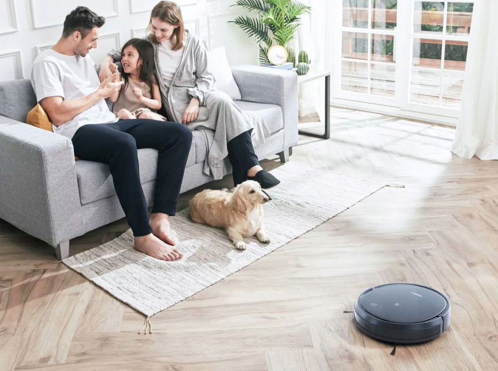 round black robotic vacuum cleaning living room floor while family sits on couch