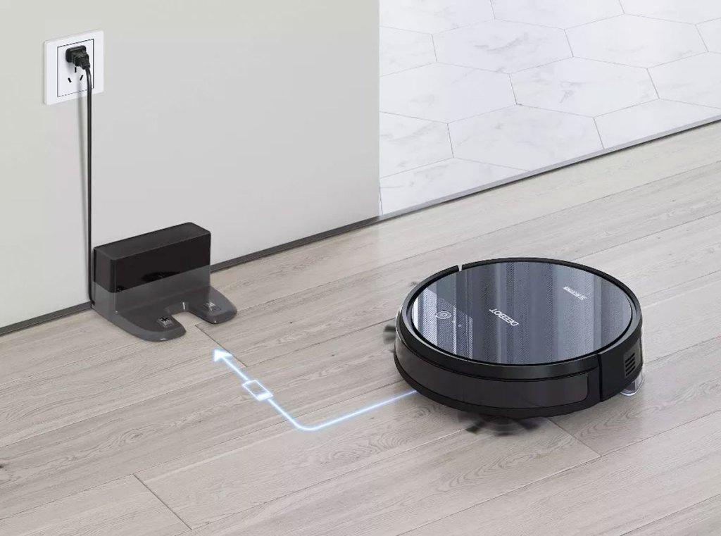round black robotic vacuum heading back to it's charging base