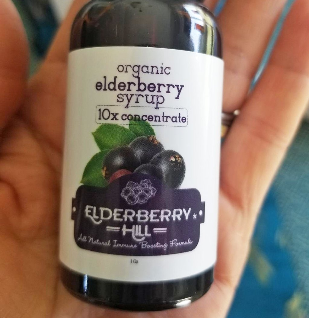 person holding a glass bottle of organic elderberry syrup in palm of hand
