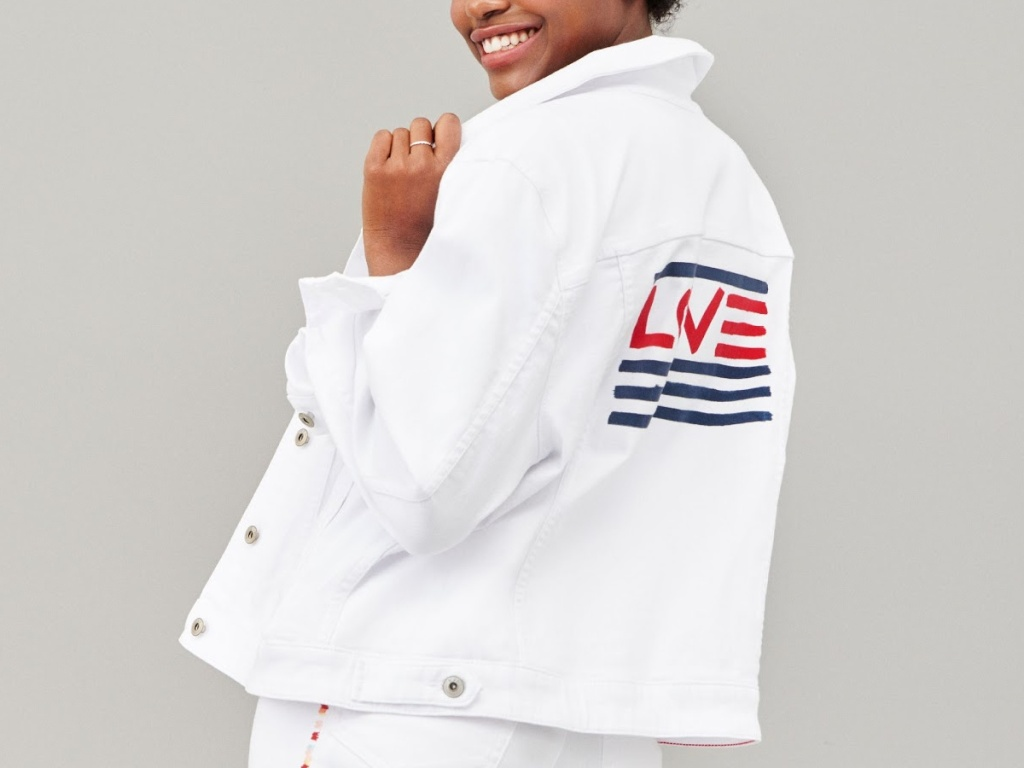 woman wearing white denim jacket with LOVE logo on back