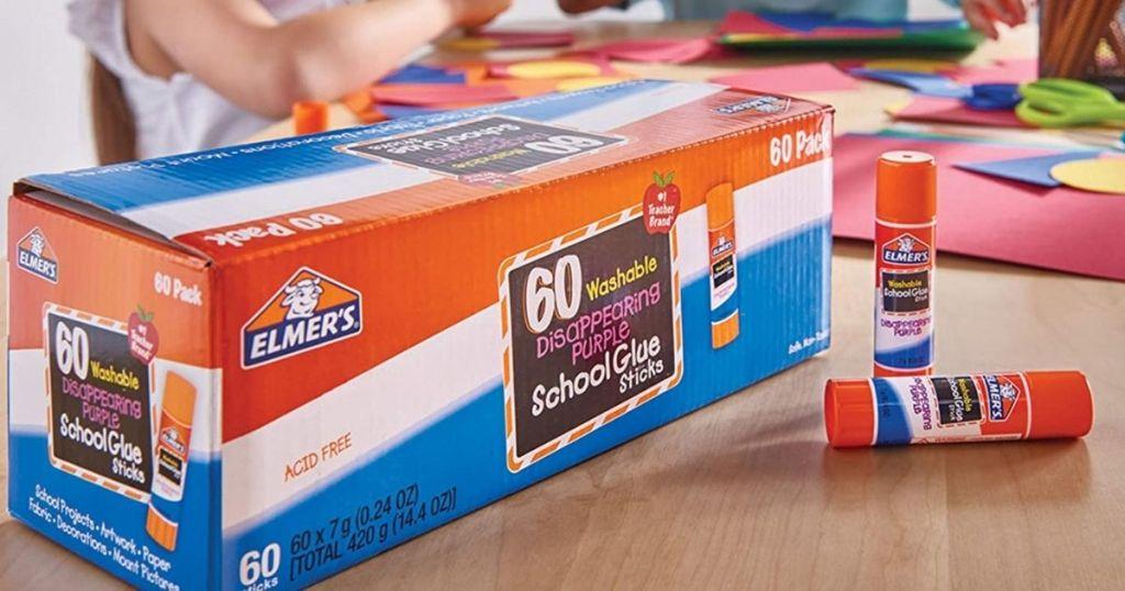 Elmers glue 60-count box wtih glue sticks on table