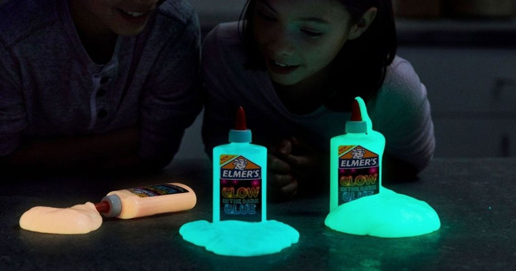 two kids in dark with three bottles of elmer's glow in the dark glue poured in front of them in orange, blue, and green colors