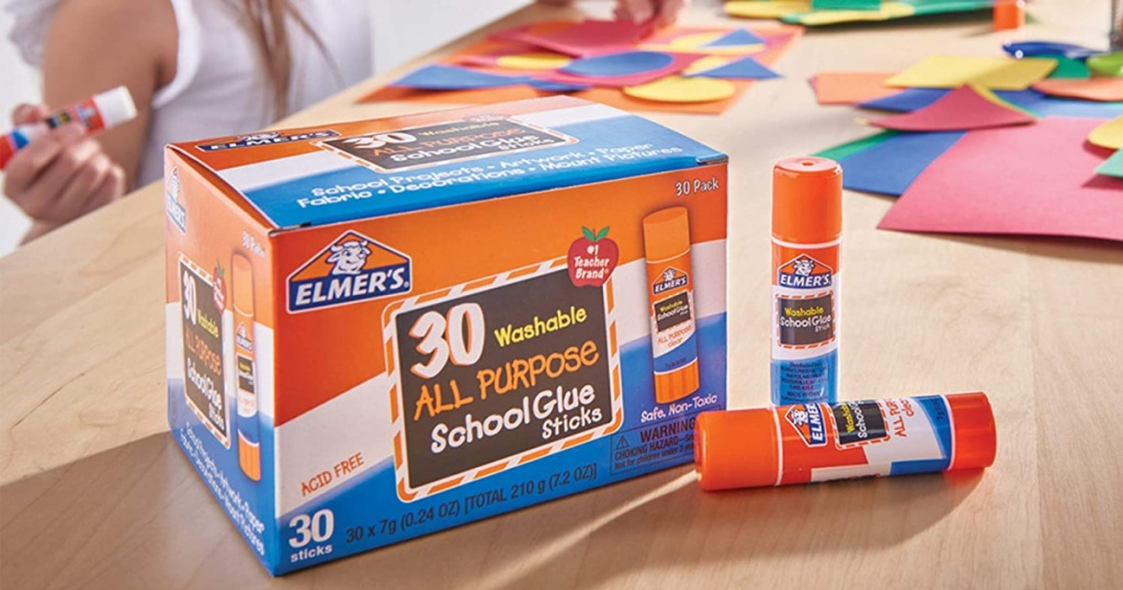 box of glue sticks on glue sticks on table with kids doing crafts
