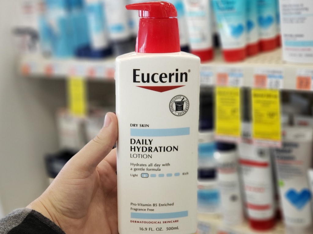 hand holding a bottle of eucerin lotion in store at cvs
