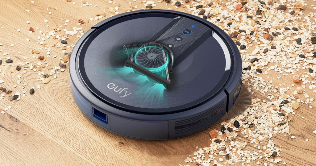 black eufy robotic vacuum cleaning up birdseed spilled on a wood floor