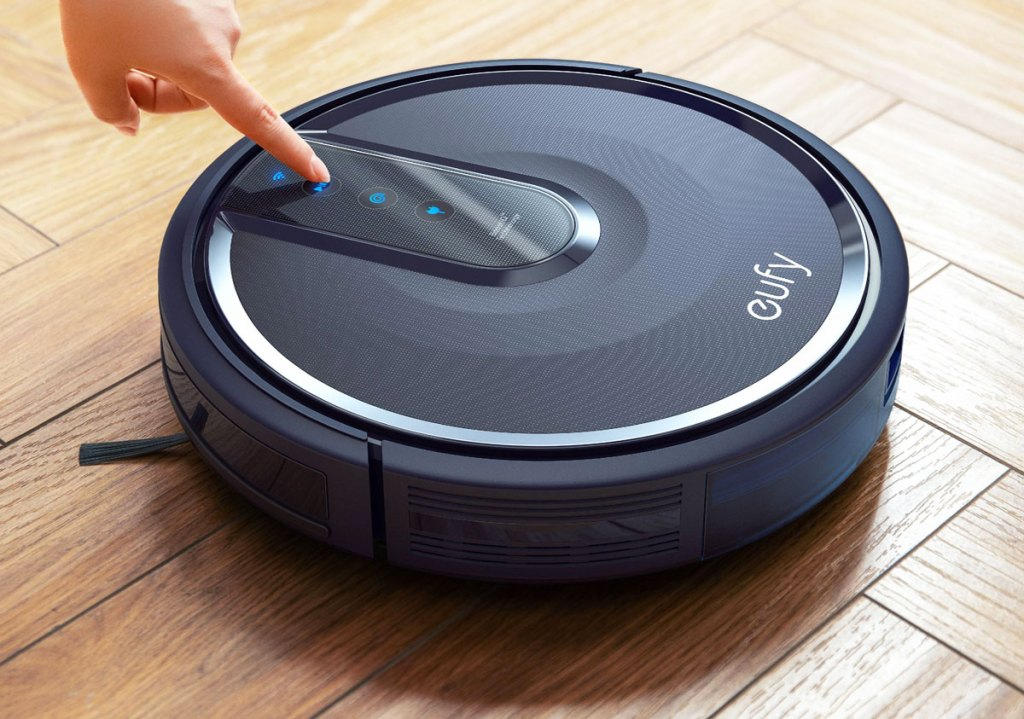 person pressing a button on a black eufy robotic vacuum on a wood floor