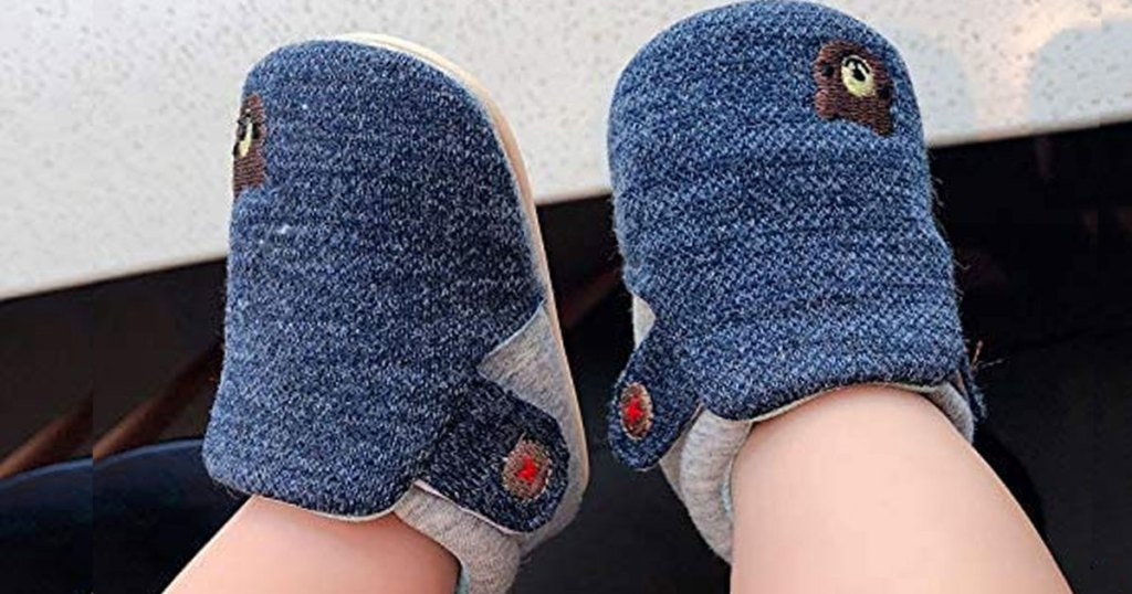 baby wearing a pair of navy blue crib shoes with embroidered brown bear on them