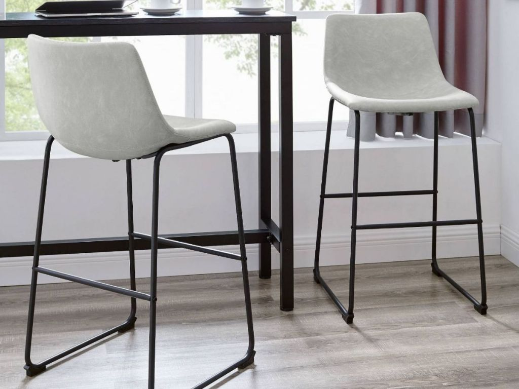 Two Leather Bar Stools next to high table