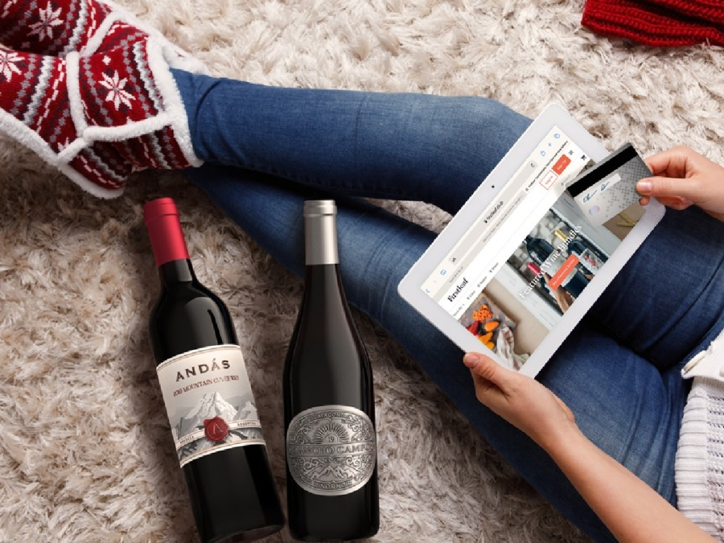 woman sitting on a carpeted floor wearing slippers next to two bottles of wine