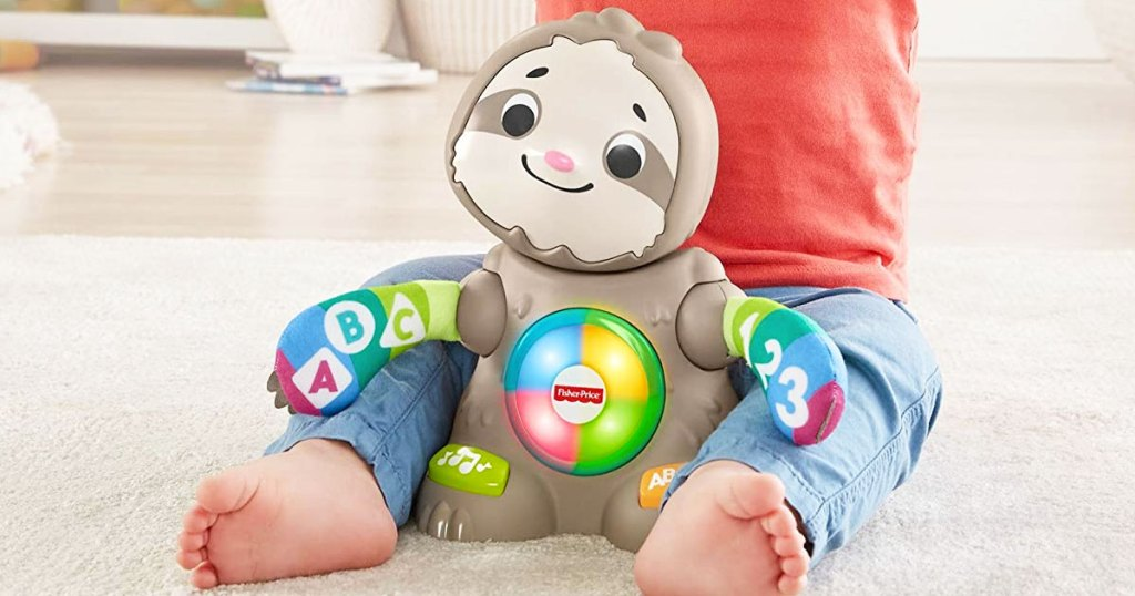 fisher price sloth toy on floor with a baby sitting behind it