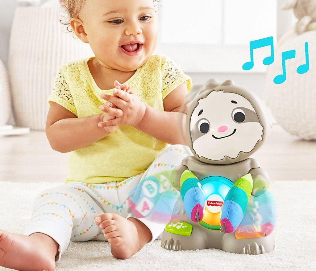 baby sitting on floor next to fisher price sloth toy that's singing and clapping its hands
