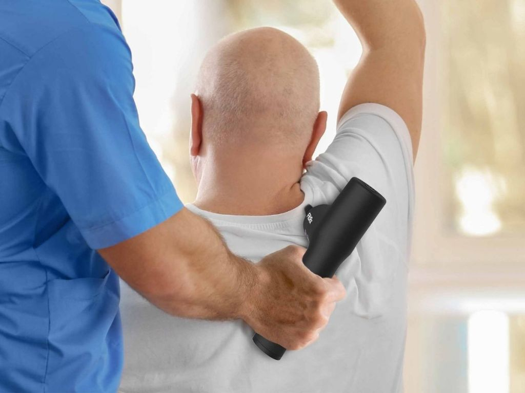 guy in scrubs holding massager to guys shoulder blade